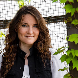 Madison Schwindenhammer posed Einfront of a wire fence and behind greenery